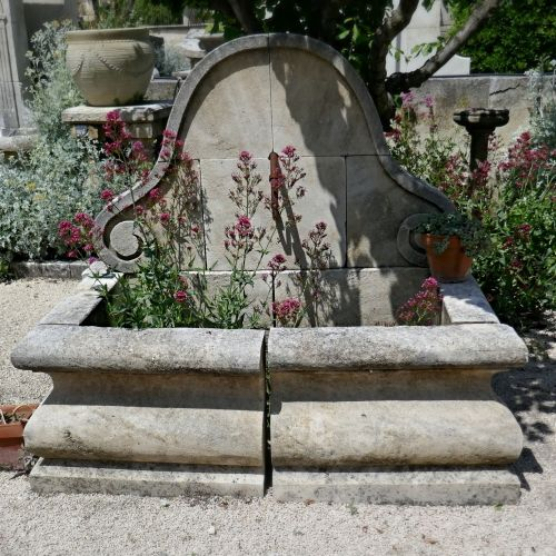 "Garden wall fountain in natural limestone carved with a ""Gendarme's hat""."