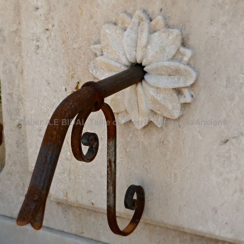 Detail of the wrought iron water outlet adorned with a beautiful hand carved rosette on the pediment of our decorative garden fountain | Alain BIDAL workshop.