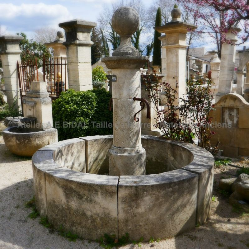 Garden fountain made of natural stone with column and round basin.