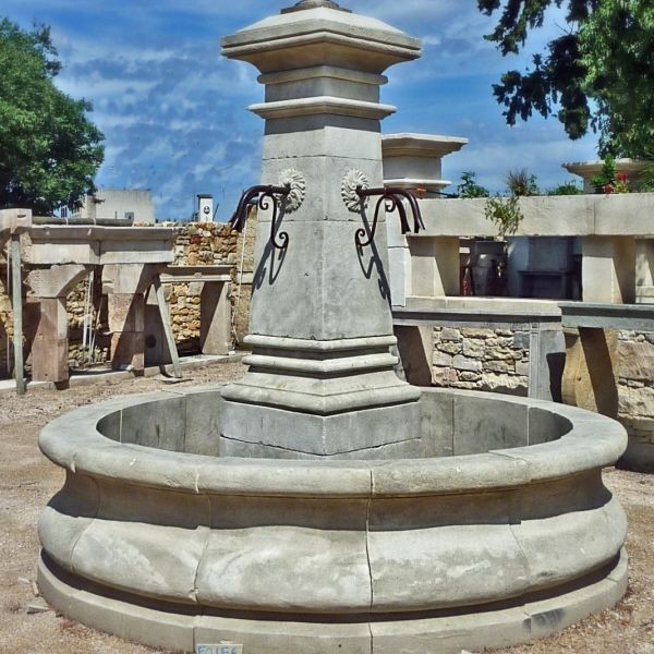 Large central stone fountain for outdoor landscaping.