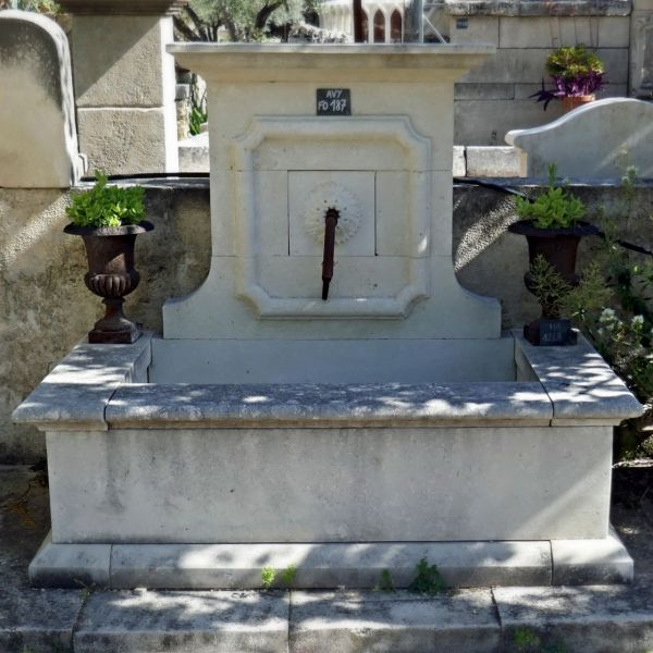 Provence stone fountain with carved pediment and wrought iron water outlet.