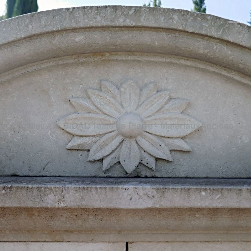 Hand carved flower on the molded cornice of our large stone fountain with lion's head.
