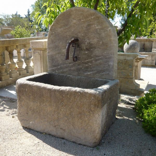 Garden wall fountain with massive trough by the stone cutting workshop Bidal in Provence.