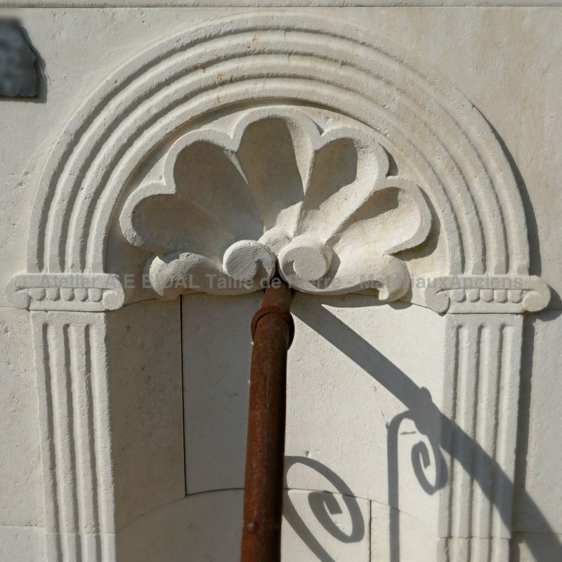 Detail of the sculptures made by hand on the pediment of our beautiful white stone wall fountain.