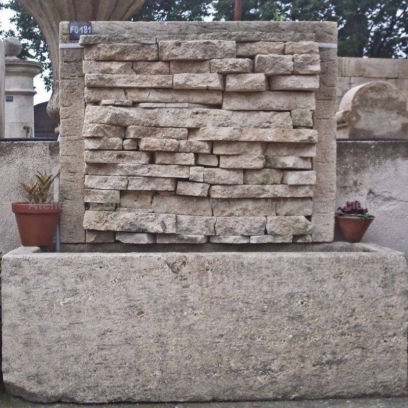 Garden wall fountain - an element of outdoor decoration in stone from Alain Bidal in Provence.