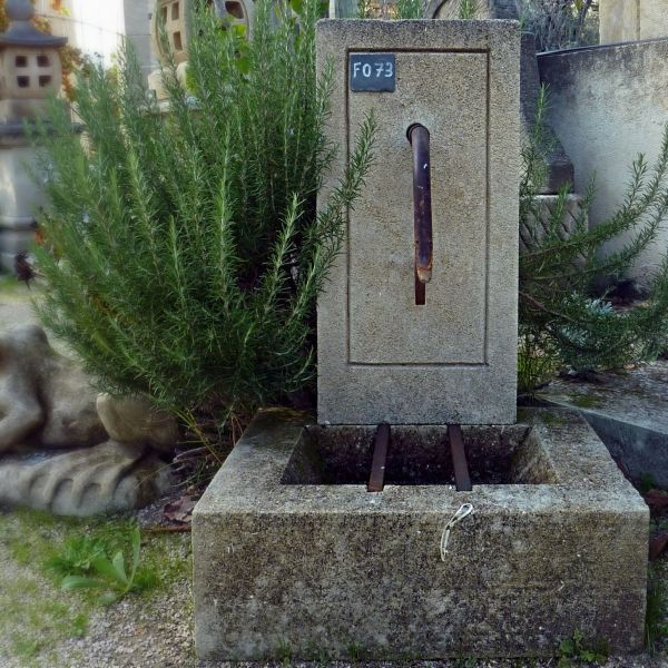 Small water point : a rustic wall fountain in carved stone