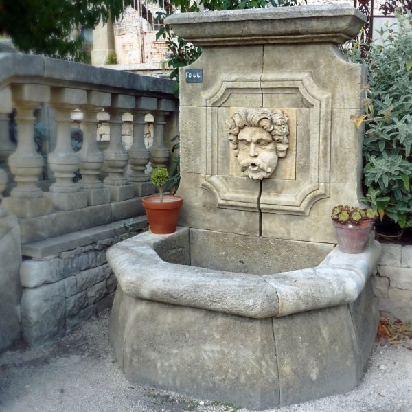 Rustic fountain with a stone sculpture representing Aeolus, the Greek God King of the Winds.