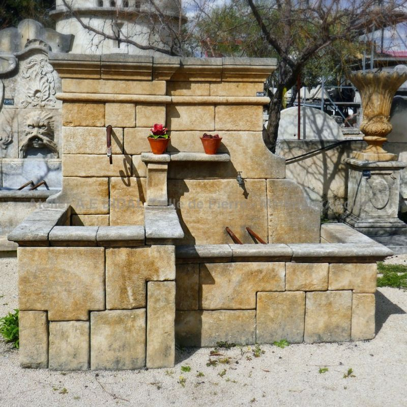 Garden fountain carved out of natural stone in the stone cutting workshops of Alain Bidal in Provence.