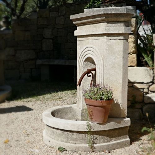 Fountain in carved stone in a rustic inpiration by the stone mason A E Bidal